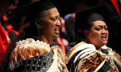 Close-up of two people performing a Karakia – Incantation, in traditional Maori cloaks