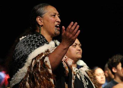Person dressed in traditional Māori cloak singing a Māori song or waiata