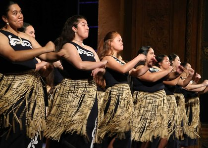 Group of women performing a waiata, dressed in full traditional Maori costume