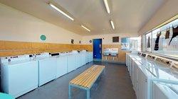 Matai, Miro, Tawa and Totara Halls's laundry with fourteen washing machines and a bench seat