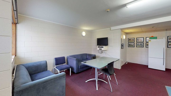 Interior of Moginie Hall's lounge with a wall mounted TV, fridge, couches and a dining table with chairs