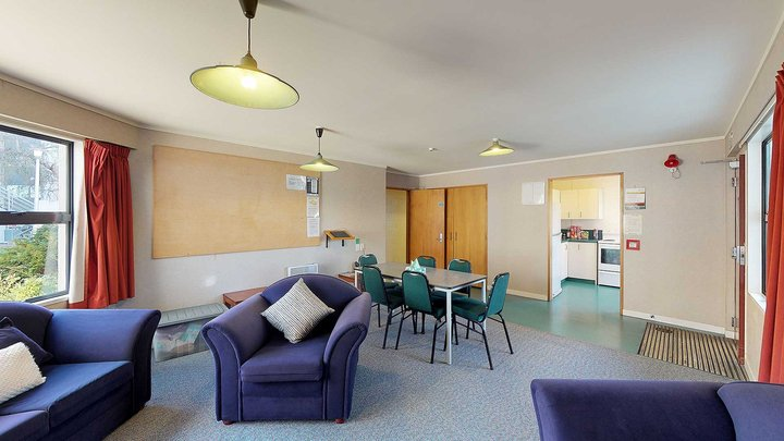 Interior of Ruahine and Tararua apartments' lounge with a couch, armchairs and a large dining table with chairs