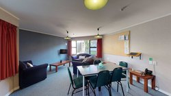 Interior of the Ruahine and Tararua apartments' lounge with armchairs, coffee tables and a dining table with chairs