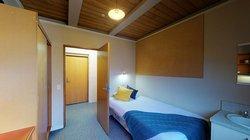 Interior of Ruahine and Tararua apartments' single bedroom with bed, hand basin, wardrobe and study desk