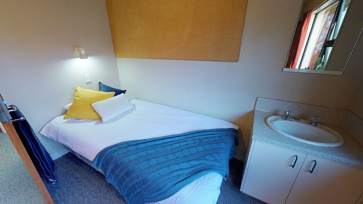 Interior of Ruahine and Tararua apartments' single bedroom with a bed and hand basin