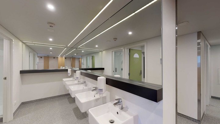 Interior of Walter Dyer Hall's bathroom with mirrors and five modern hand basins