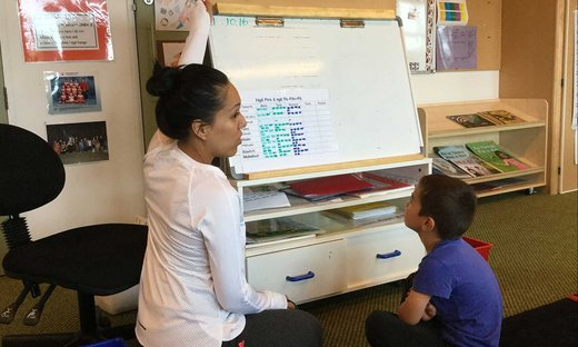 Student teacher sitting on the floor with a young boy, using a whiteboard to teach te Reo