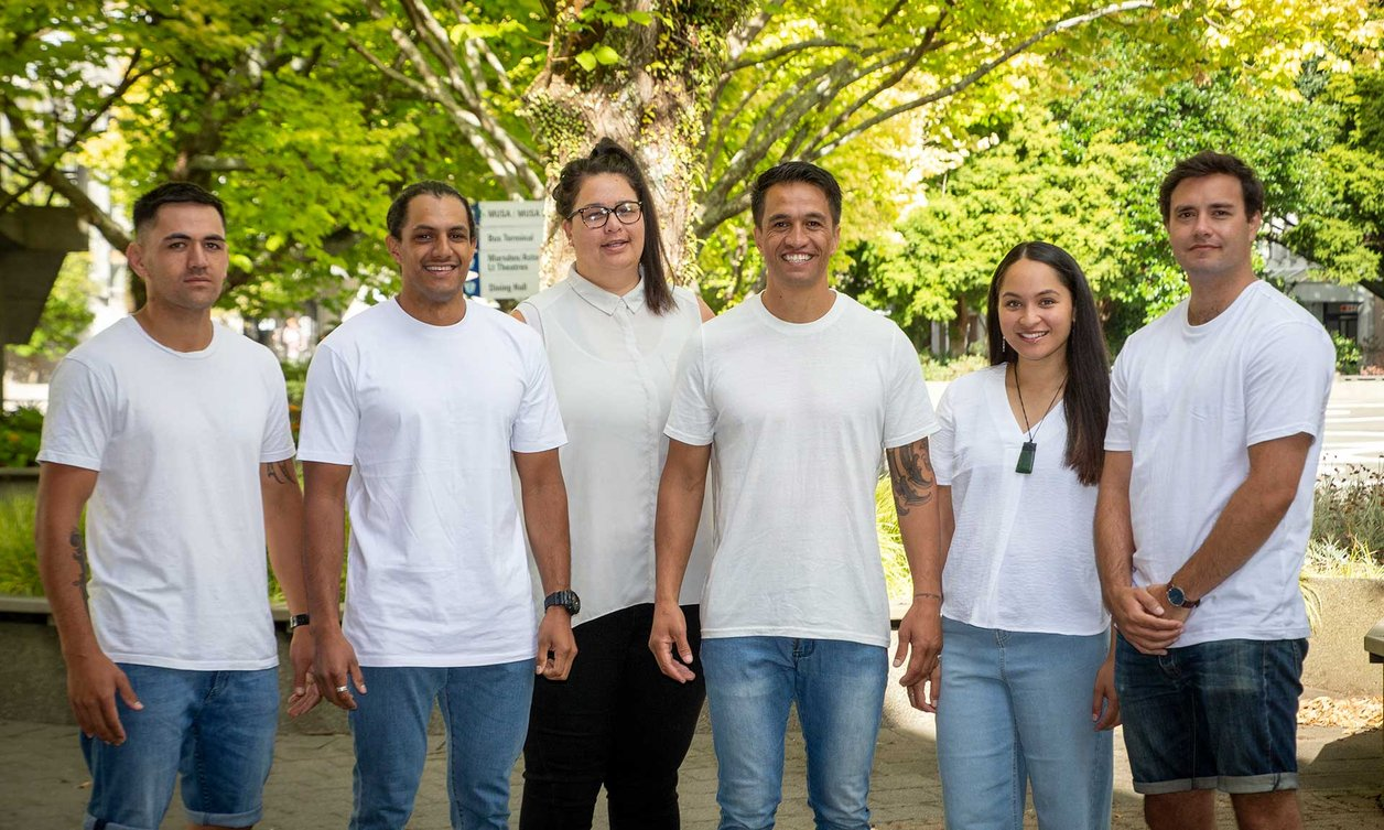 Group of six people of the Te-Rau-Tauawhi team standing outside, all wearing white t-shirts and denim pants