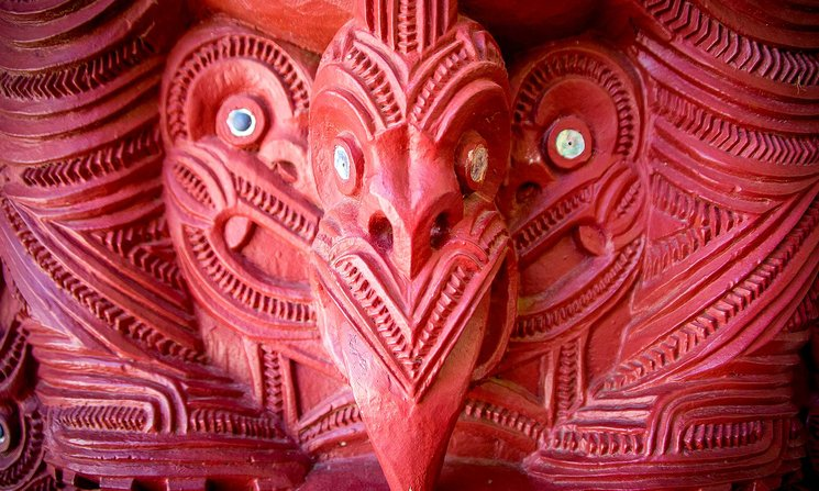 Close-up of red traditional Māori wood carving at a marae
