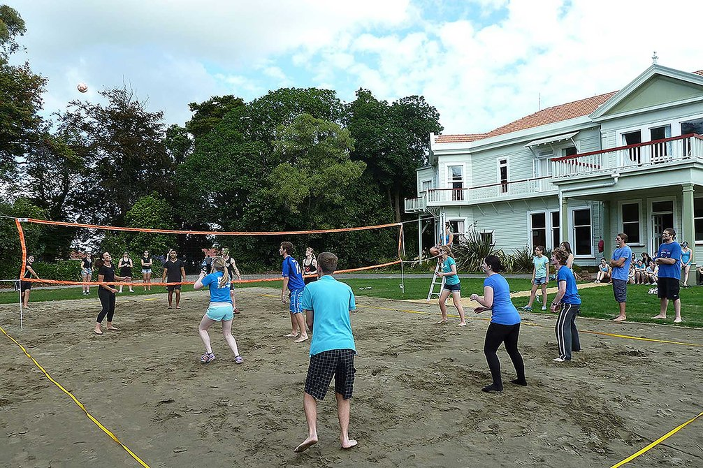 Students playing a game of volleyball with Fergusson Hall in the background
