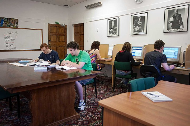 Two students reading at a large desk and three students using desktop computers in Fergusson Hall's study room