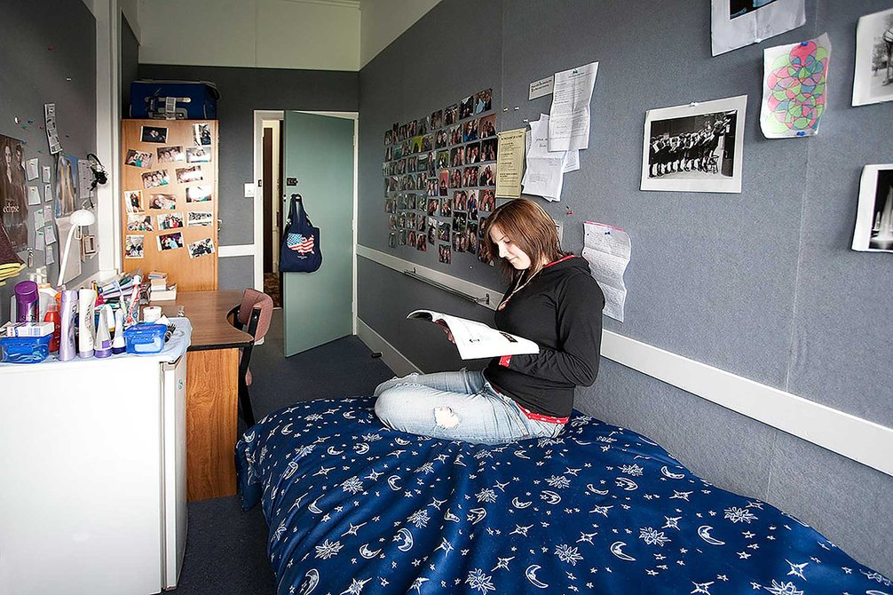 Student sitting on a bed, reading, in a single bedroom in Fergusson Hall
