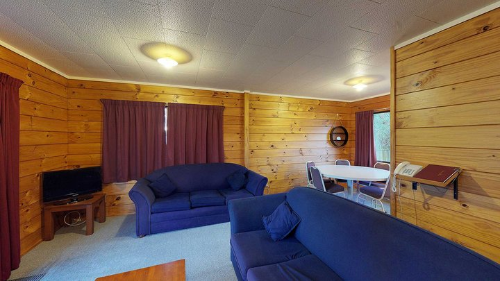 Interior of Atawhai Flats lounge with tv, table and couches