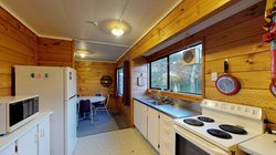 Interior of Atawhai Flats kitchen with table and chairs, fridge, bench, sink and oven