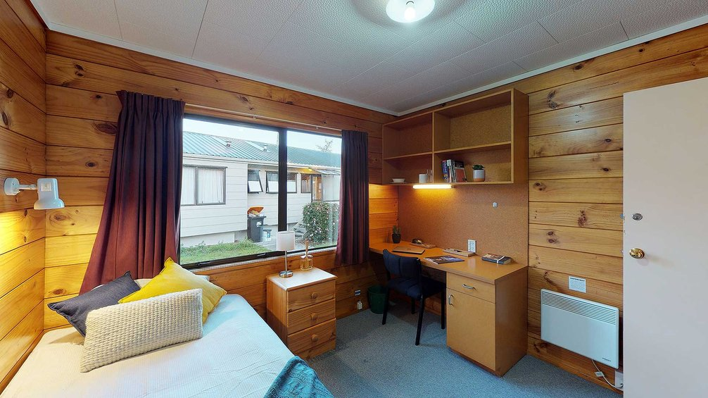 Interior of Atawhai Flats single bedroom with bed, drawers, and built-in furniture