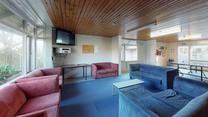 Interior of City and Egmont Courts' lounge with wall mounted TV, table tennis table and couches