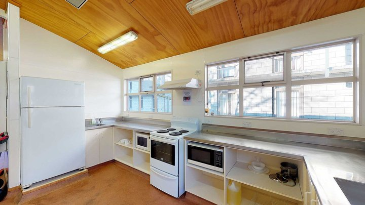 Interior of City and Egmont Courts' kitchen with large fridge, oven, microwave and bench-tops