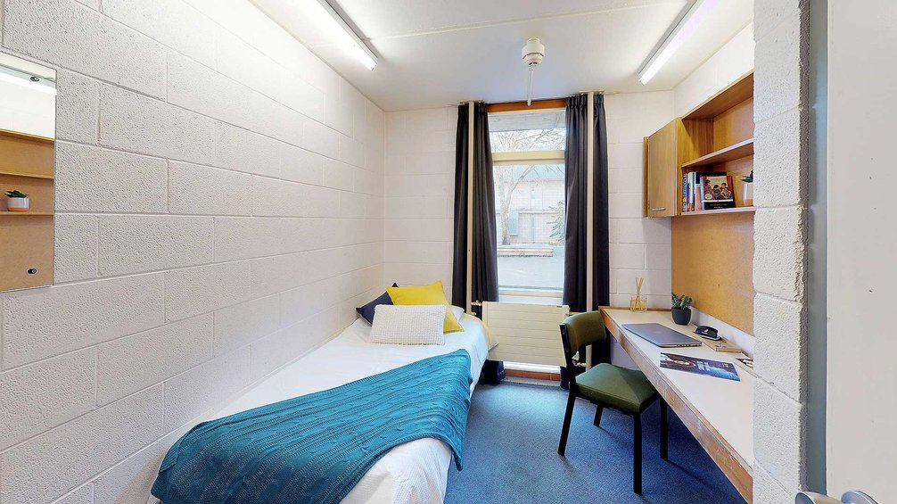 Interior of City and Egmont Courts' single room with a bed, window, heater, built-in storage and a study desk with a chair