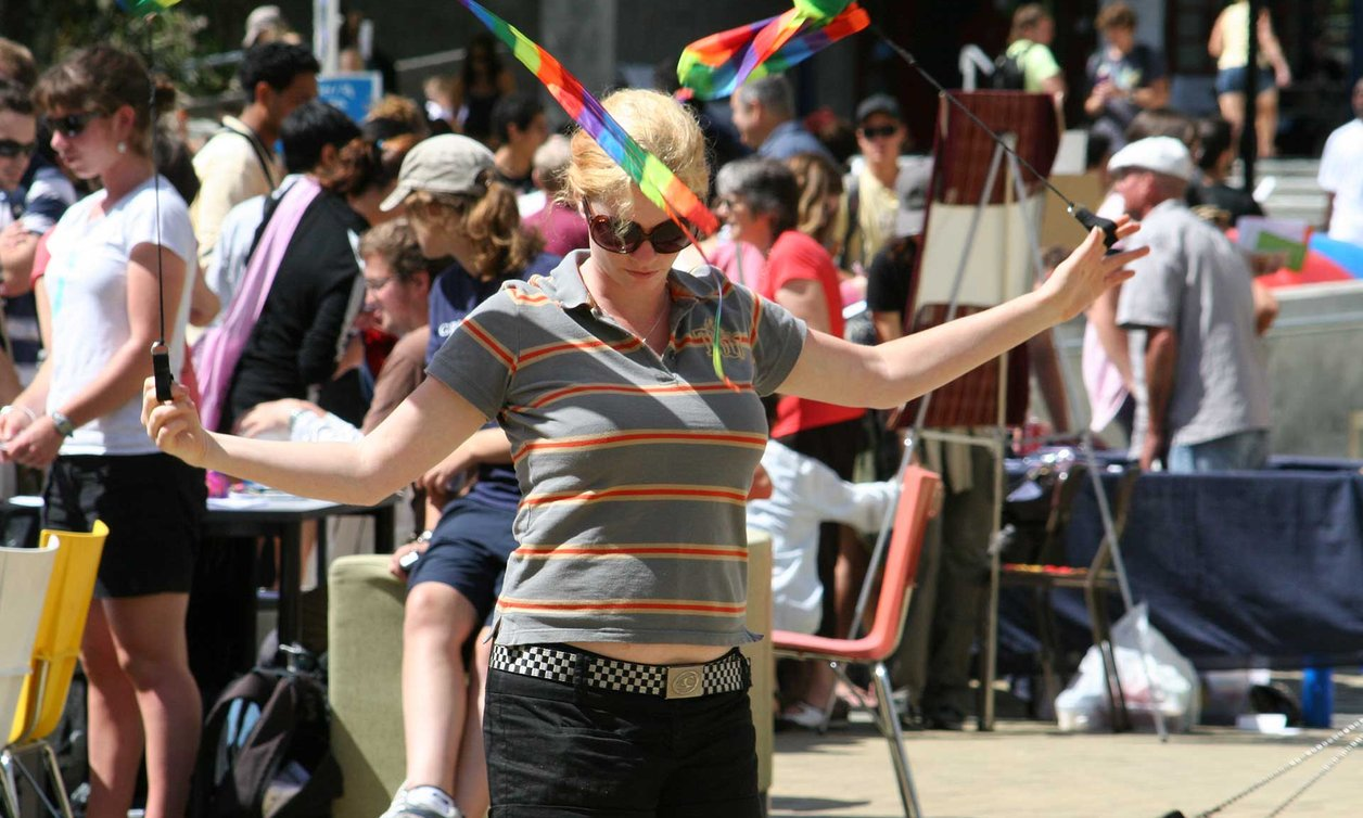 Student twirling two narrow rainbow flags, with a crowd of students in the background