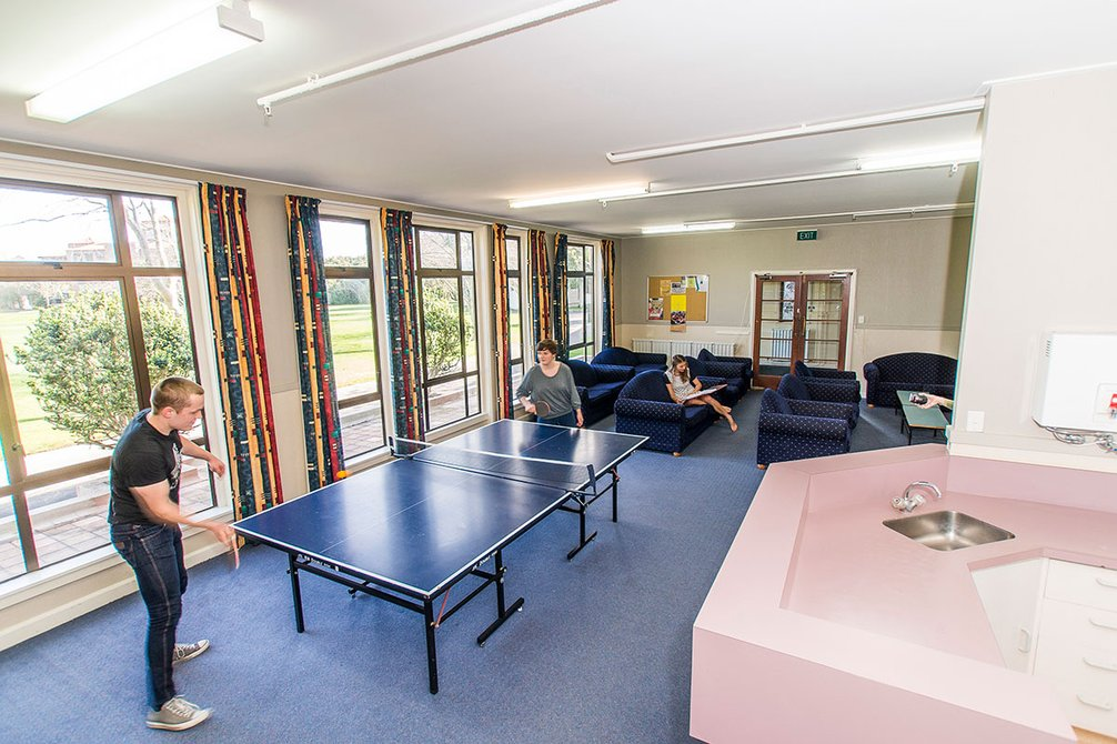 McHardy Hall common room with students playing table tennis with a person sitting on one of the many couches in the background