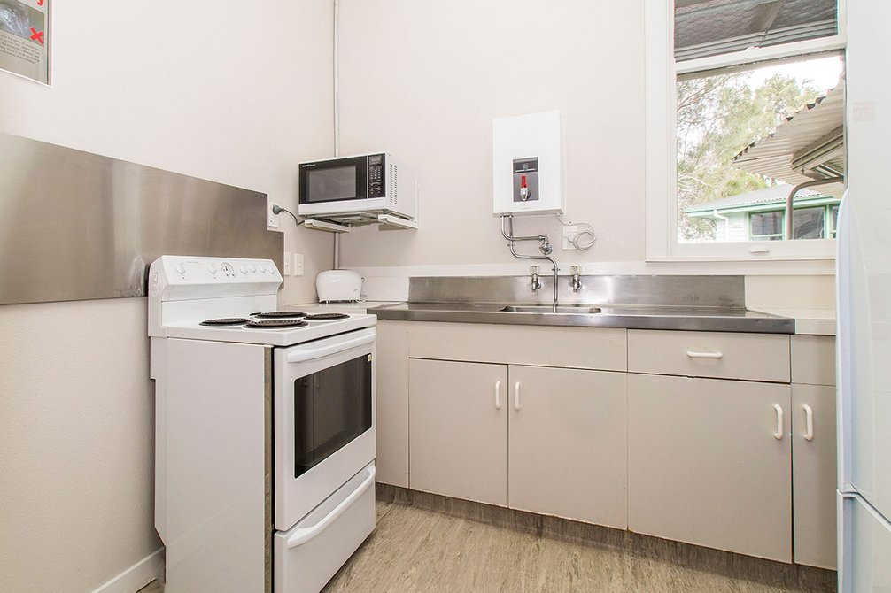 Interior of Craiglockhart Hall's small kitchen with bench top, oven and microwave