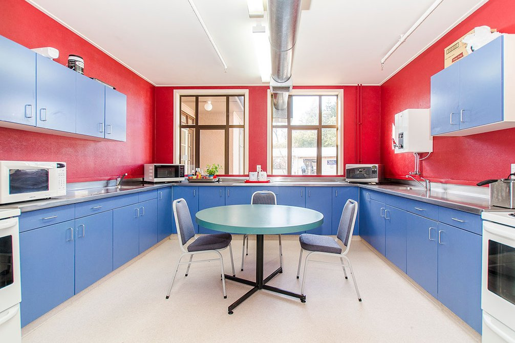 Brightly painted red and blue kitchen in McHardy Hall with built-in cupboards, three microwaves, two ovens and a dining table with chairs