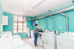 Laundry room in McHardy Hall with a person using one of the many washing machines