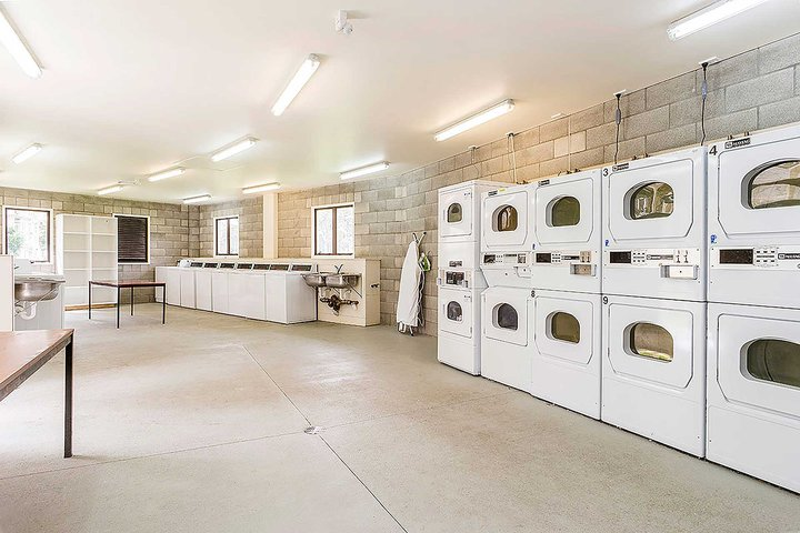 Interior of Kairanga and Rotary Courts large laundry with tables and multiple washing machines