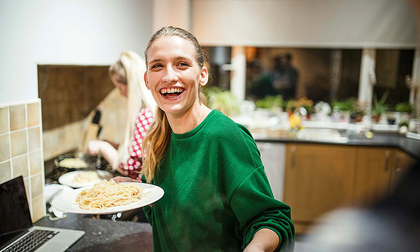 Close-up of a person smiling, holding a plate of pasta, inside a kitchen