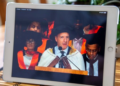 Close-up of a tablet screening graduation livestream