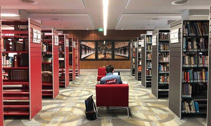 A student sitting on a chair between the stacks of Massey's Auckland Library