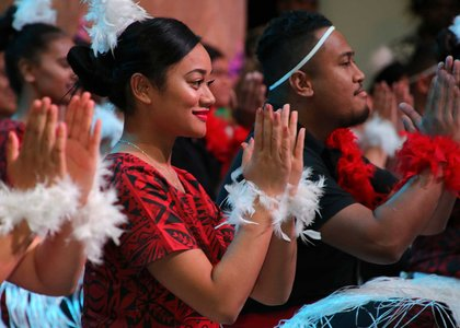 Close-up of person clapping while seated as part of a group giving a traditional Pacific performance