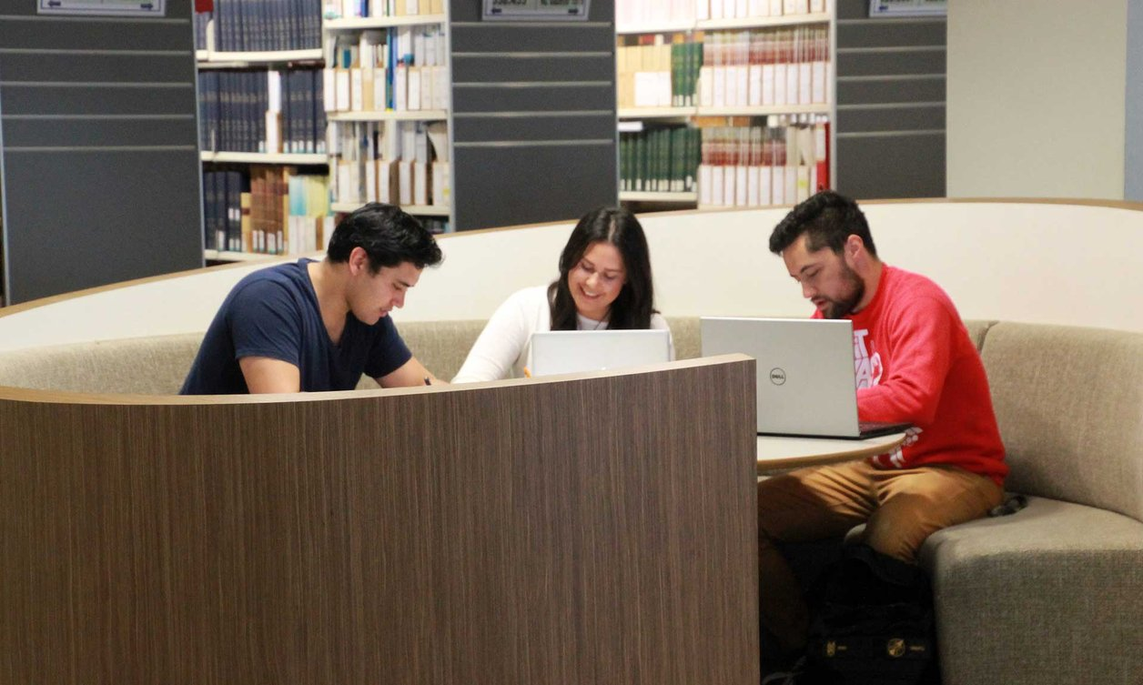 Three students sitting in a semi-circle, using laptops while studying, with bookshelves in the background